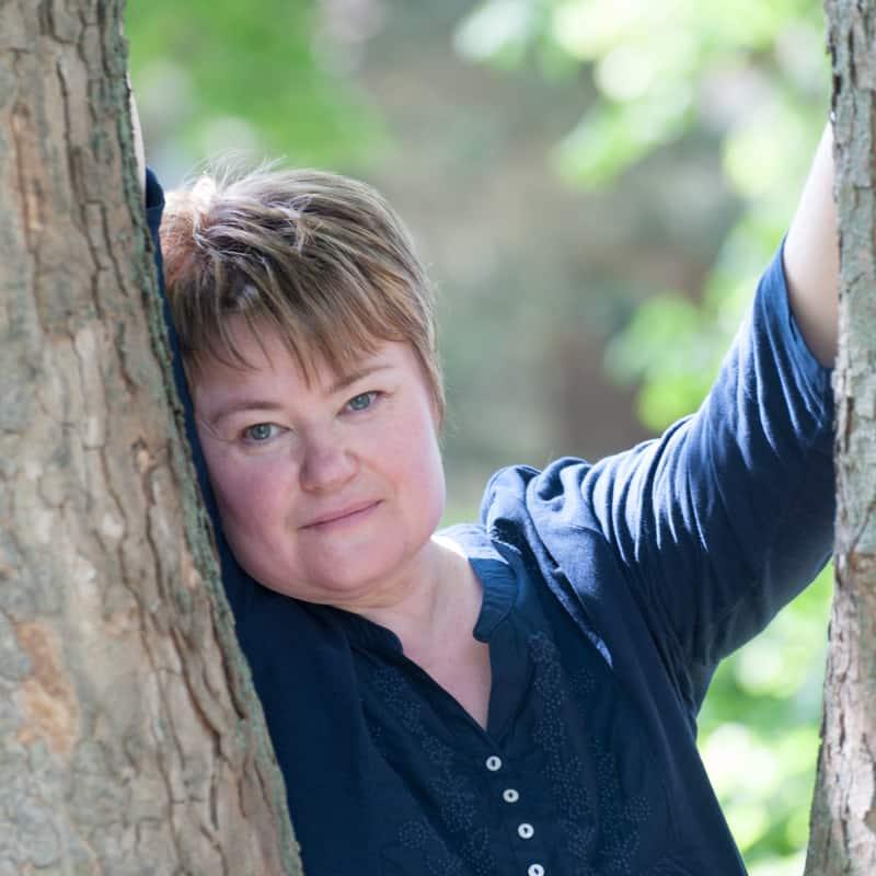 Eine Frau lehnt träumend an einem Baum, Anja & Udo