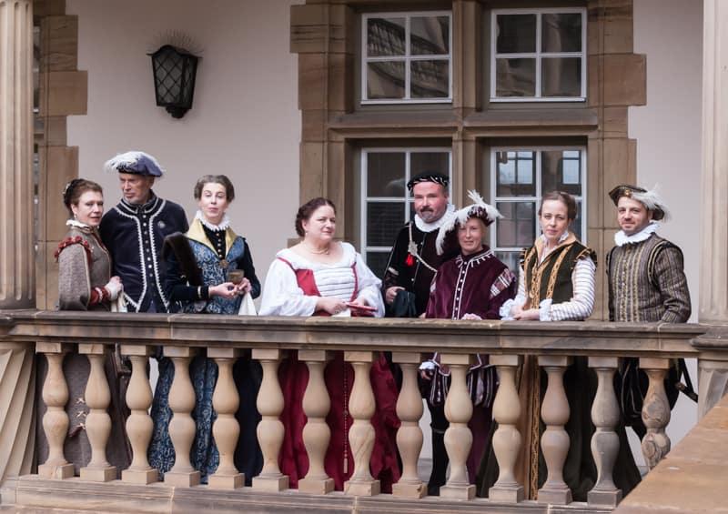 8 Menschen mit historischen Kleidern schauen in die Kamera