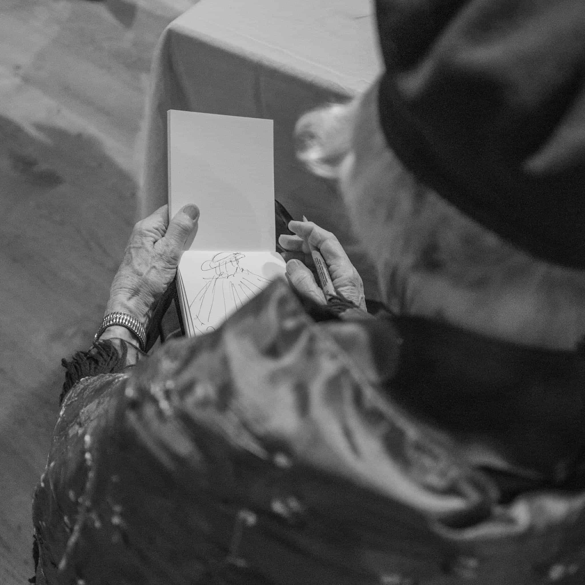 Alte Dame zeichnet, über Schulter geschaut